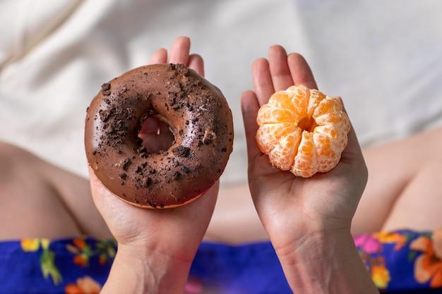 Mani di giovane donna all'aperto sotto gli alberi in un parco, decidendo tra mangiare ciambelle dolci o un frutto mandarino. calorie o frutta.