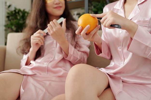 Mani della giovane donna che sbucciano e tagliano l'arancia quando la sua amica lima le unghie sullo sfondo
