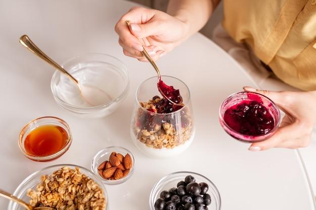 Mani di giovane donna che mette marmellata di ciliegie appetitosa fatta in casa in vetro con muesli e panna acida mentre si prepara lo yogurt per la colazione