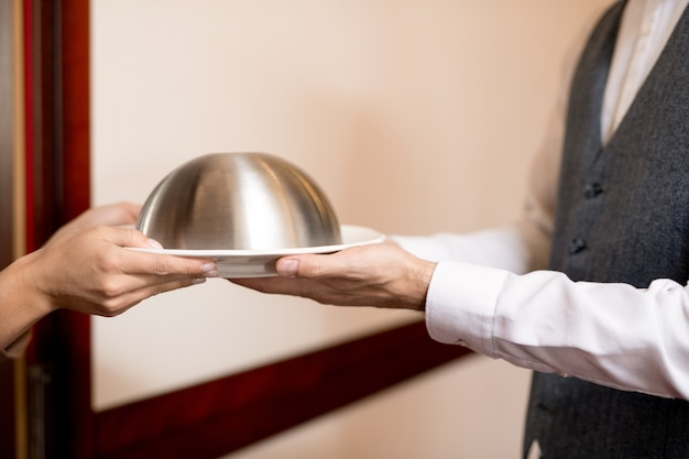 Mani di giovane donna che cattura cloche con il cibo del ristorante dal cameriere elegante attraverso la porta aperta della camera d'albergo
