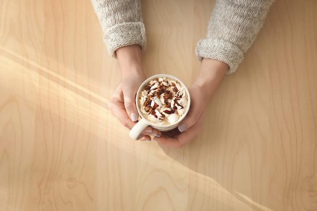 Mani di una giovane donna con una tazza di gustosa bevanda al cacao su fondo di legno
