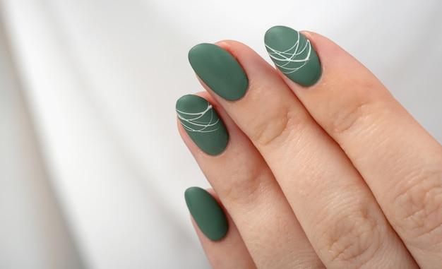 Mani di una giovane donna con unghie opache verde oliva su sfondo grigio chiaro. manicure, pedicure concetto di salone di bellezza. copia spazio per testo o logo. smalto gel e motivo a ragnatela bianca astratta.