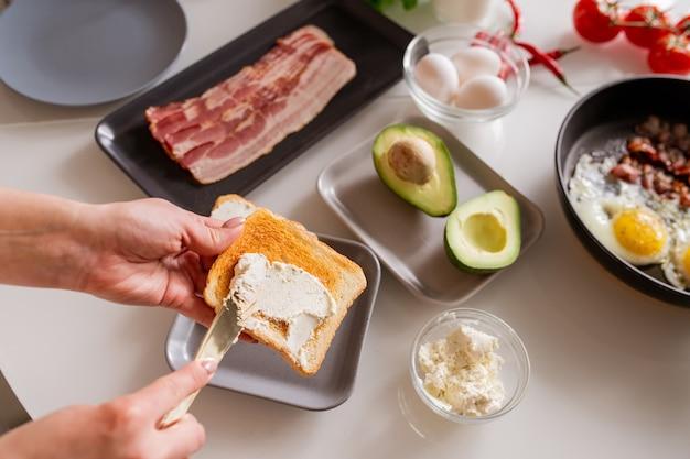 Le mani della giovane donna con il coltello spalmando prodotti lattiero-caseari su pane tostato serviti sul tavolo da cucina con avocado fresco, pancetta, uova e pomodori