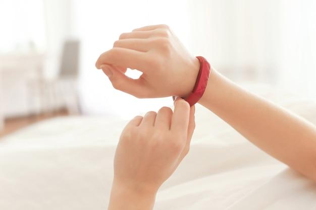 Mani di giovane donna con inseguitore del sonno sdraiata a letto a casa