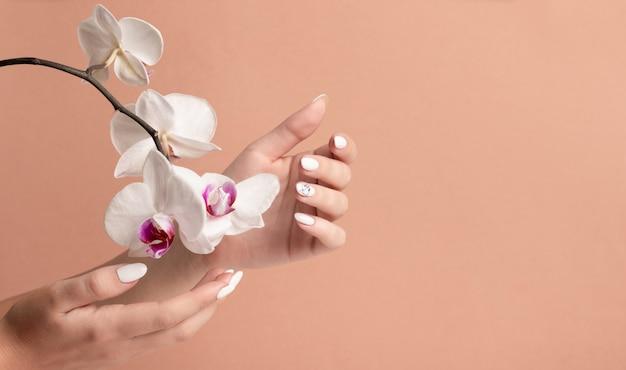 Mani di una giovane donna con unghie lunghe bianche su fondo beige con fiori di orchidea.