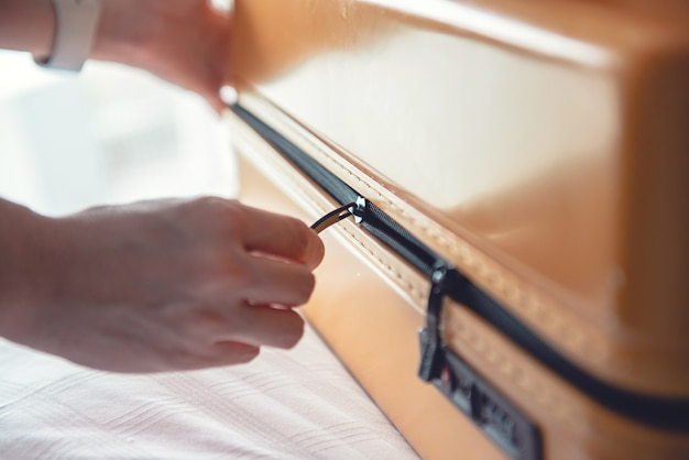 Mani che chiudono una borsa da viaggio valigia da viaggio sul letto in camera da letto
