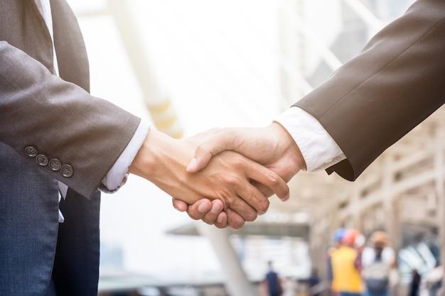 Accordo di stretta di mano dell'uomo d'affari con la partnership in città