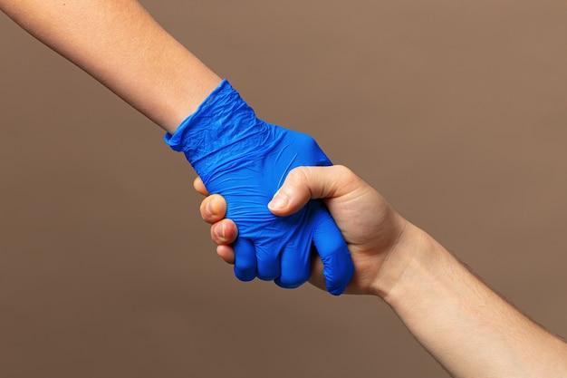 Stretta di mano in guanti blu, concetto di aiuto. igiene personale durante una pandemia