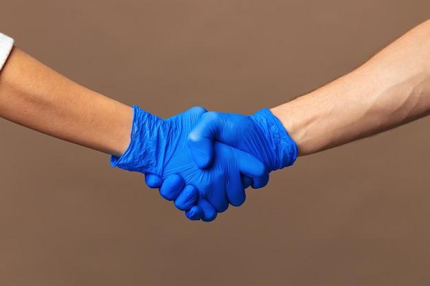 Stretta di mano in guanti blu, concetto di aiuto.