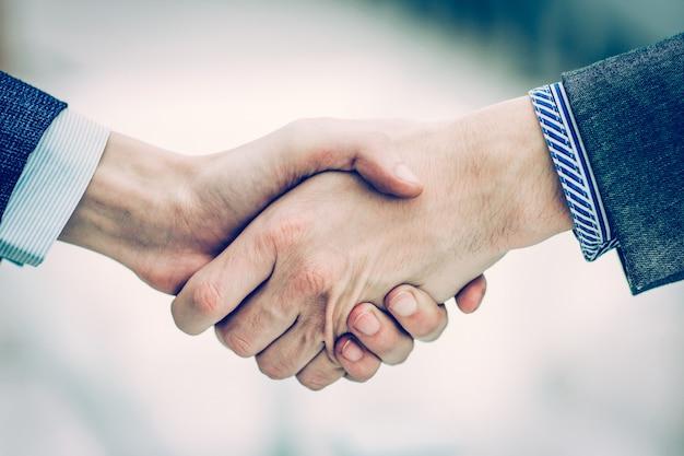 Stretta di mano dei partner commerciali su sfondo chiaro sfocato.la foto ha uno spazio vuoto per il testo