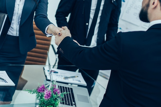 Stretta di mano dei partner commerciali alla riunione vicino al desktop in un ufficio moderno. la foto ha uno spazio vuoto per il testo