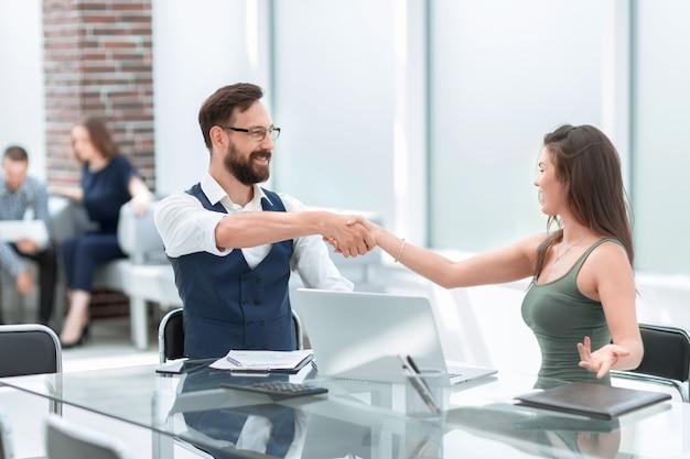 Partner commerciali della stretta di mano alla scrivania dell'ufficio .concetto di cooperazione