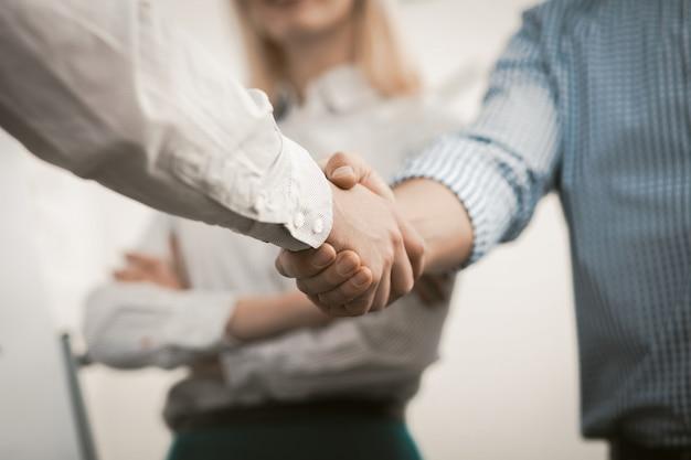 Stretta di mano di uomini d'affari. due uomini in abiti da cerimonia si stringono la mano in accordo alla riunione d'affari in ufficio. colpo da vicino