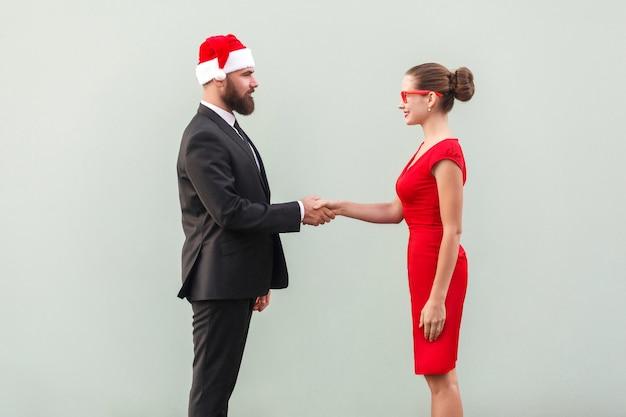 Stretta di mano, festeggia un buon contratto. uomo e donna ben vestiti. foto in studio, sfondo grigio