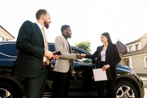 Stretta di mano di un cliente, giovane uomo d'affari africano e commesso, giovane donna caucasica al cortile della sala d'esposizione dell'automobile all'aperto. soci commerciali di due uomini che comprano nuova automobile