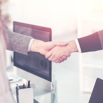 Stretta di mano tra il cliente e il manager dell'azienda vicino al posto di lavoro nell'ufficio moderno.