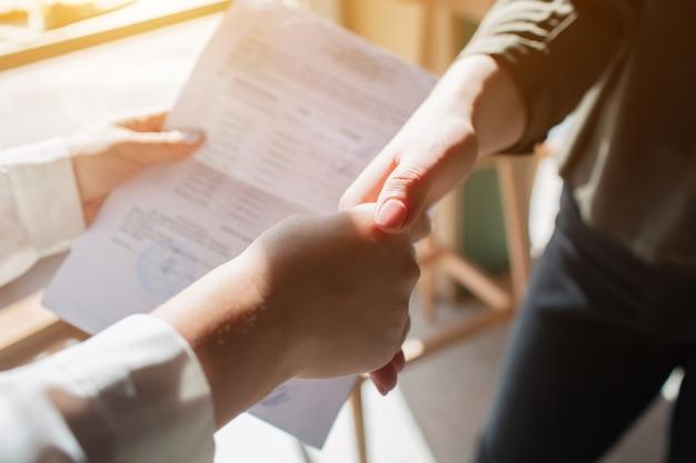 Primo piano della stretta di mano la giovane donna tiene in mano un documento e fa un affare