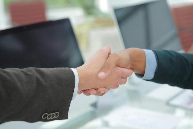 Stretta di mano partner finanziari su una scrivania in ufficio