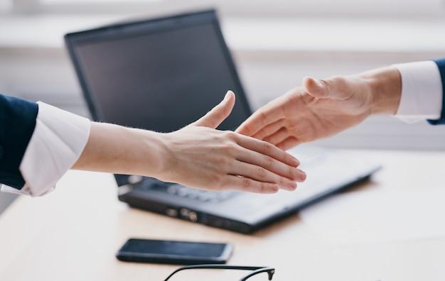 Finestra di lavoro di ufficio del computer portatile delle mani che gesturing della stretta di mano