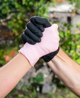 Stretta di mano, saluto in guanti protettivi medici