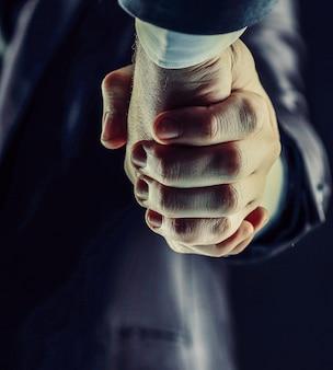 Stretta di mano - mano su uno sfondo scuro con tonalità calde