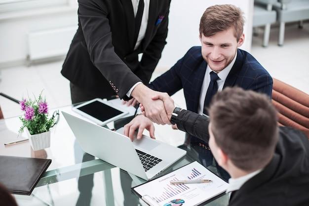 Handshake manager e il cliente dopo la discussione del contratto finanziario sul posto di lavoro in ufficio