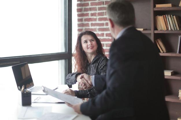 Gestore e cliente della stretta di mano seduti alla tua scrivania in ufficio.