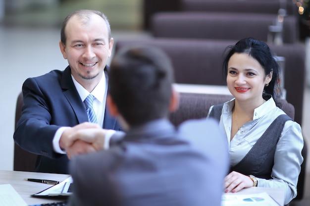 Handshake manager e cliente in un moderno ufficio.incontri e collaborazioni.