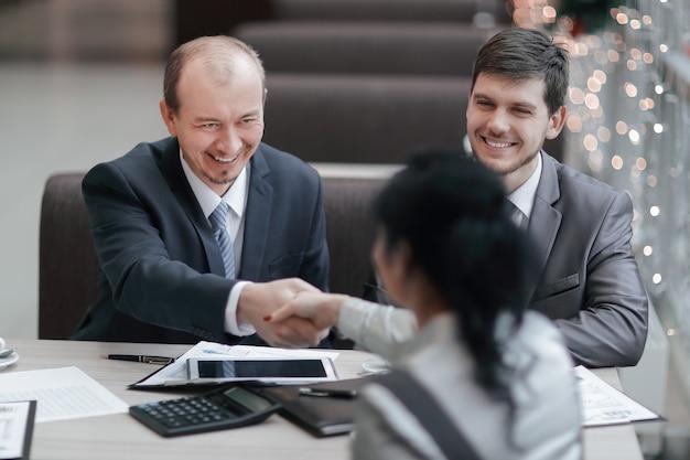 Handshake manager e cliente in un ufficio moderno, incontri e collaborazioni.