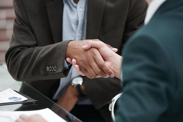 Partner commerciali della stretta di mano sullo sfondo del posto di lavoro