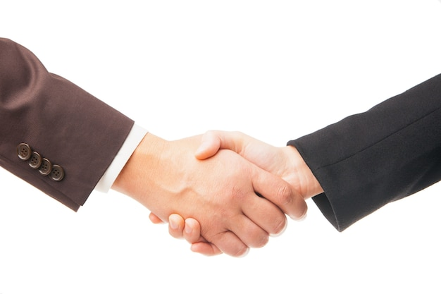 Stretta di mano di due uomini d'affari in abiti scuri, primo piano, isolato su sfondo bianco
