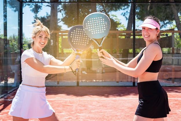 Stretta di mano del giocatore di paddle tennis di due donne