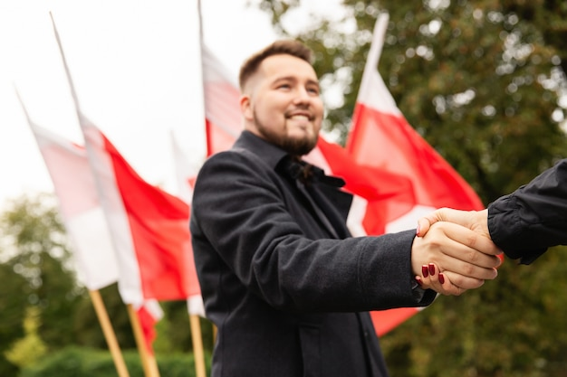 Stretta di mano con le bandiere della polonia dietro