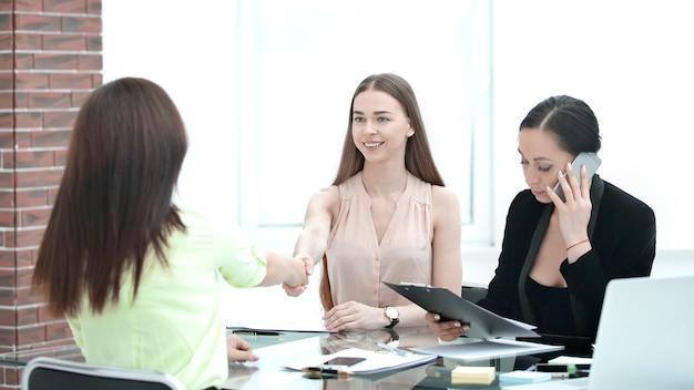 Stretta di mano di giovani partner commerciali in una riunione di lavoro in ufficio.