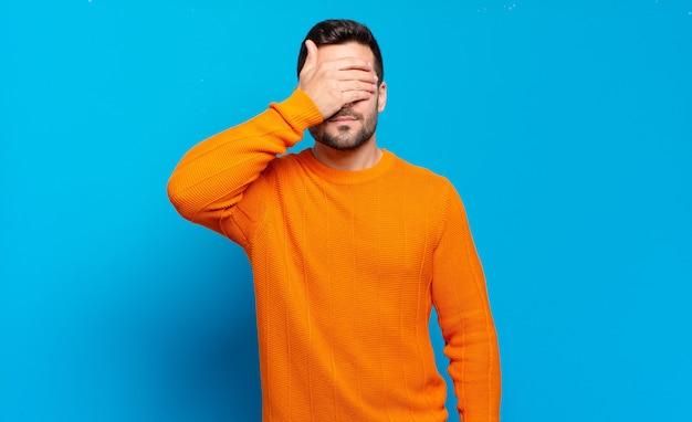 Bell'uomo biondo adulto che copre gli occhi con una mano sentendosi spaventato o ansioso, chiedendosi o aspettando ciecamente una sorpresa