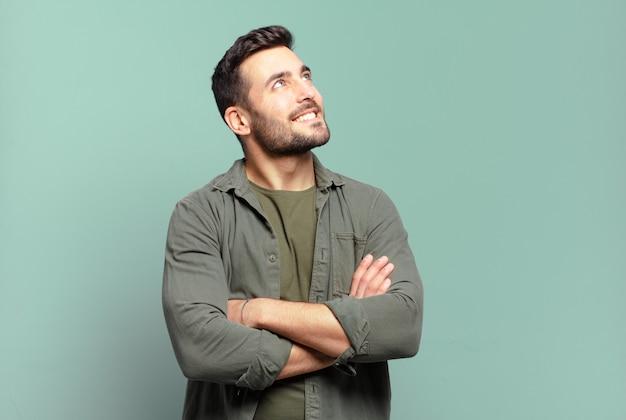 Bell'uomo biondo adulto che si sente felice, orgoglioso e speranzoso, chiedendosi o pensando, alzando lo sguardo per copiare lo spazio con le braccia incrociate