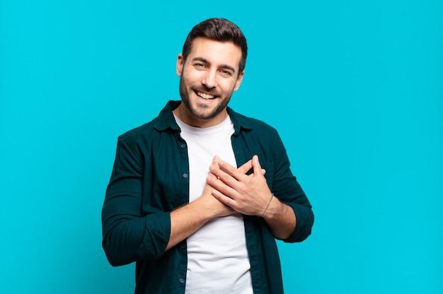 Bell'uomo biondo adulto che si sente romantico, felice e innamorato, sorride allegramente e si tiene per mano vicino al cuore