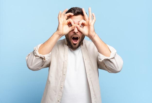 Bell'uomo adulto biondo che si sente scioccato, stupito e sorpreso, tenendo gli occhiali con uno sguardo stupito e incredulo