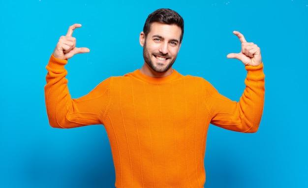 Bell'uomo adulto biondo che incornicia o delinea il proprio sorriso con entrambe le mani, guardando positivo e felice, concetto di benessere