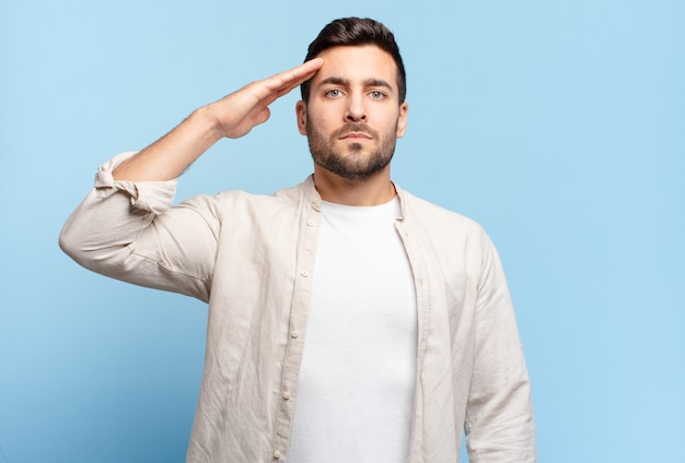 Uomo biondo adulto bello che saluta la telecamera con un saluto militare in un atto di onore e patriottismo, mostrando rispetto