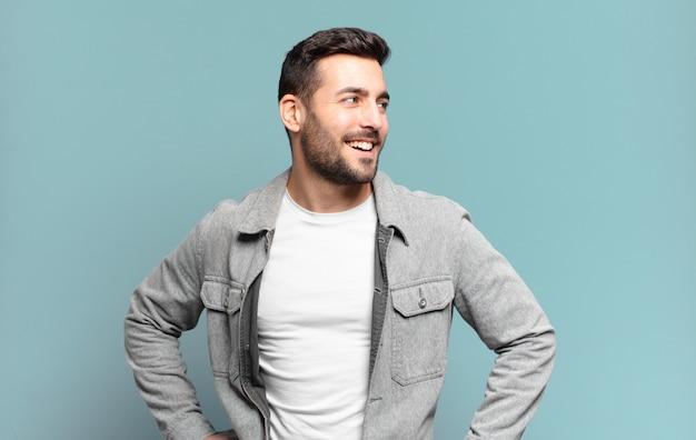 Bell'uomo adulto biondo che sembra felice, allegro e fiducioso, sorridendo con orgoglio e guardando a lato con entrambe le mani sui fianchi