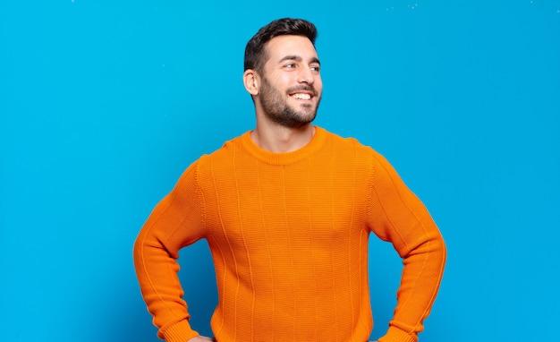Bell'uomo biondo adulto che sembra felice, allegro e fiducioso, sorride con orgoglio e guarda dalla parte con entrambe le mani sui fianchi hip