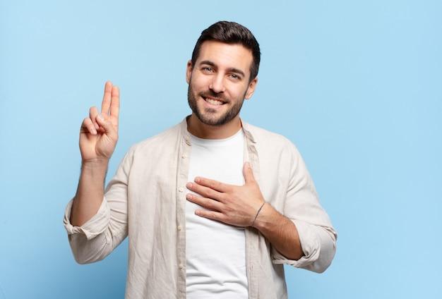 Bell'uomo biondo adulto che sembra felice, fiducioso e degno di fiducia, sorridente e che mostra il segno della vittoria, con un atteggiamento positivo positive