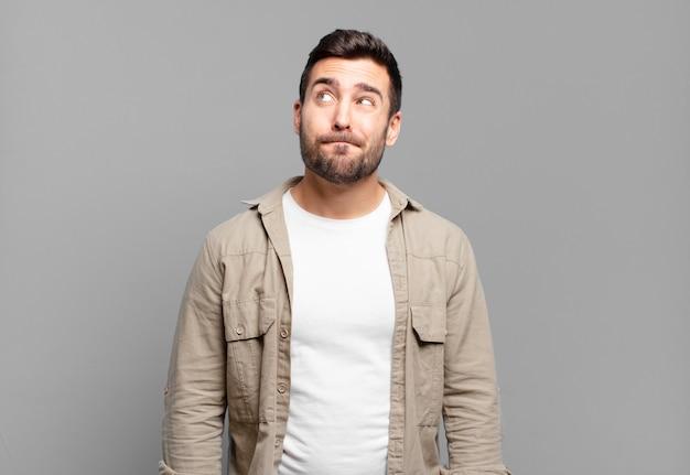 Bell'uomo biondo adulto che sembra perplesso e confuso, chiedendosi o cercando di risolvere un problema o pensando