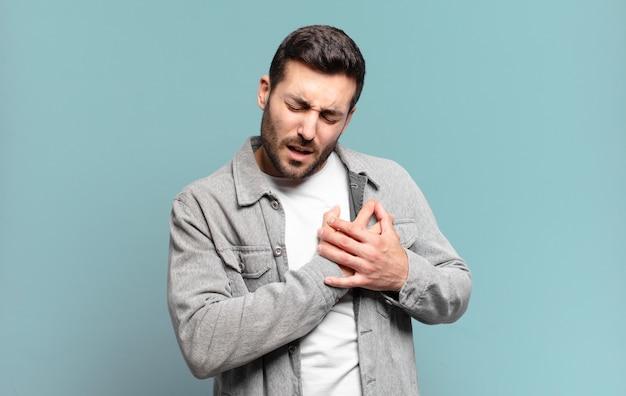 Bell'uomo biondo adulto che sembra triste, ferito e affranto, tenendo entrambe le mani vicino al cuore, piangendo e sentendosi depresso
