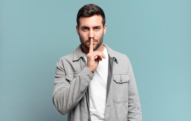 Bell'uomo biondo adulto che sembra serio e si incrocia con il dito premuto sulle labbra chiedendo silenzio o silenzio, mantenendo un segreto