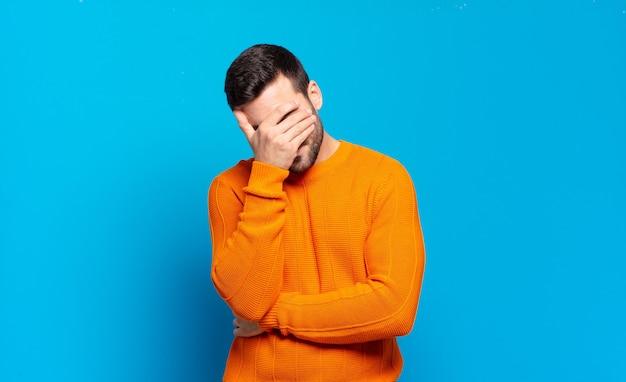 Bell'uomo biondo adulto che sembra stressato, vergognoso o sconvolto, con mal di testa, che copre il viso con la mano
