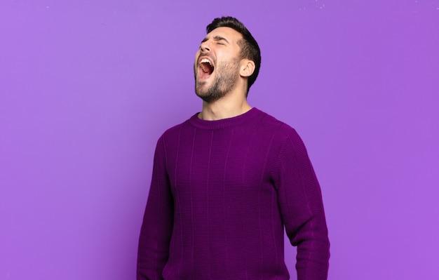 Bell'uomo biondo adulto che urla furiosamente, grida in modo aggressivo, sembra stressato e arrabbiato