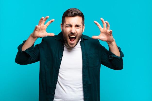 Bell'uomo adulto biondo che grida in preda al panico o rabbia, scioccato, terrorizzato o furioso, con le mani accanto alla testa