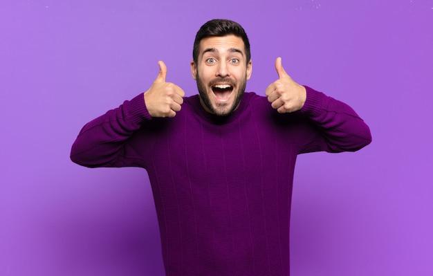 Bell'uomo biondo adulto che sorride ampiamente e sembra felice, positivo, fiducioso e di successo, con entrambi i pollici in su